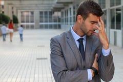 Homme indécis ayant un mal de tête important photographie stock libre de droits