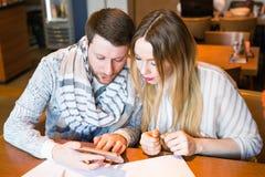 Homme indépendant avec la femme travaillant dans le restaurant Communication masculine et femelle au sujet des projets ou des str images stock