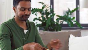 Homme indien déballant les plats à emporter à la maison banque de vidéos