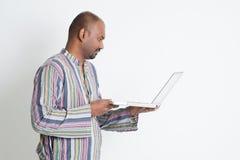 Homme indien de vue de profil à l'aide de l'ordinateur Image libre de droits