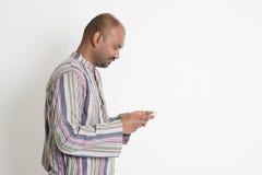 Homme indien occasionnel mûr employant le media social Image stock