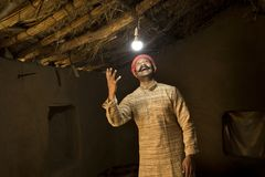 Homme indien rural ravi sur l'électricité atteignant sa maison photos libres de droits
