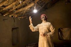 Homme indien rural ravi sur l'électricité atteignant sa maison photographie stock libre de droits