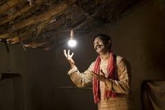 Homme indien rural ravi sur l'électricité atteignant sa maison photo stock