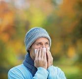 Homme infecté soufflant son nez en papier de soie de soie photographie stock