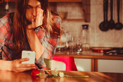 Homme inquiété avec rose et le téléphone portable Photographie stock libre de droits