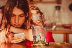 Homme inquiété avec rose et le téléphone portable Images stock