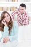 Homme inquiété jaloux scrutant au-dessus de l'épaule de son amie Photo libre de droits
