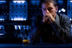 Homme inquiété s'asseyant au bar Photo stock