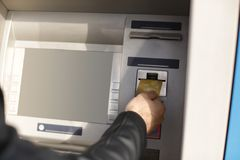 Homme insérant la carte de crédit dans le distributeur automatique de billets image libre de droits