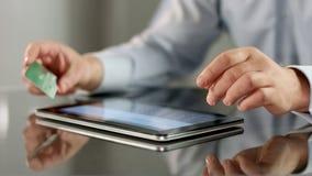 Homme insérant le numéro de carte de crédit sur l'application de comprimé, opérations bancaires en ligne, compte image libre de droits