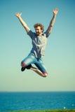Homme insouciant sautant par l'eau d'océan de mer Images libres de droits