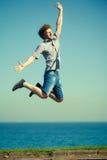 Homme insouciant sautant par l'eau d'océan de mer Photos libres de droits