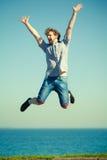 Homme insouciant sautant par l'eau d'océan de mer Images stock