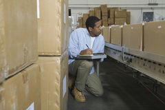 Homme inspectant des boîtes sur la bande de conveyeur Photographie stock libre de droits