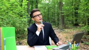 Homme inspiré créant des idées, se reposant au bureau dans le parc, connexion avec la nature image libre de droits