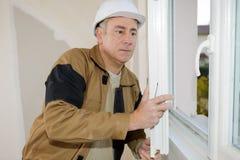 Homme installant des abat-jour de fenêtre dans la maison Image stock
