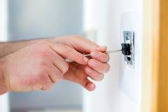 Homme installant l'interrupteur de lampe avec le tournevis photos libres de droits