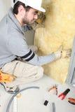 Homme installant l'isolation Photos libres de droits