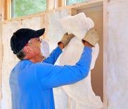 Homme installant l'isolation de fibre de verre Photos libres de droits