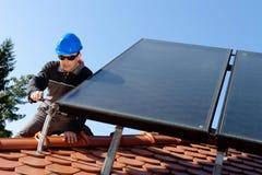 Homme installant la casserole photovoltaïque d'énergie de substitution  photographie stock