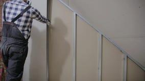 Homme installant la feuille de plaque de plâtre pour murer pour la construction de pièce de grenier banque de vidéos