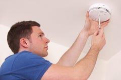 Homme installant la fumée ou le détecteur de monoxyde de carbone Image stock