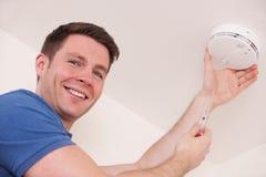 Homme installant la fumée ou le détecteur de monoxyde de carbone Images stock