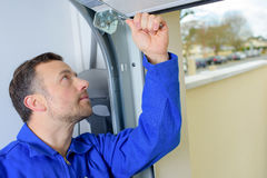 Homme installant la porte de garage photo libre de droits