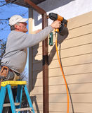 Homme installant la voie de garage avec le canon de clou Images libres de droits