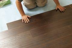 Homme installant le plancher en bois en stratifié neuf image stock