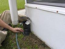 Homme installant les connecteurs résidentiels de tuyau de descente d'eaux ménagères Image libre de droits