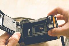 Homme installant une cartouche de film de photo photo stock