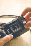 Homme installant une cartouche de film de photo images stock