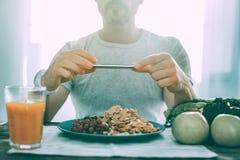 Homme intéressé enthousiaste faisant une photo dans la cuisine photos stock