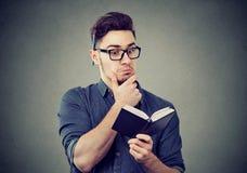 Homme intéressé lisant un bloc-notes photos stock