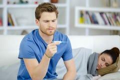 Homme intéressé prenant la température en difficulté de wifes dans leur chambre à coucher Image libre de droits