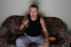 Homme intéressé regardant la TV avec de la bière et des pommes chips Images libres de droits
