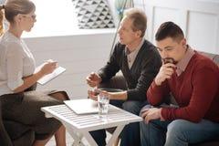 Homme intéressé triste parlant à un psychologue Images stock