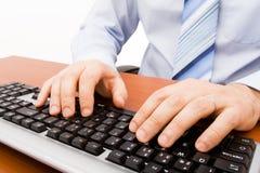 Homme introduisant au clavier l'ordinateur photographie stock