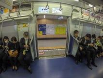 Homme japonais de salaire dormant ou à l'aide de leur téléphone dans le whil de souterrain photos stock