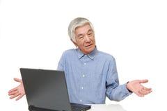 Homme japonais supérieur à l'aide de l'ordinateur semblant confus Images stock