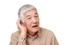 Homme japonais supérieur avec la main derrière l'oreille écoutant étroitement Photo stock