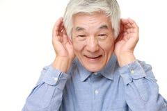 Homme japonais supérieur avec la main derrière l'oreille écoutant étroitement Image stock