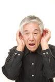 Homme japonais supérieur avec la main derrière l'oreille écoutant étroitement Photo libre de droits