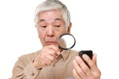 Homme japonais supérieur avec la presbytie Image stock