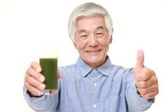 Homme japonais supérieur avec le jus de légumes vert Images stock