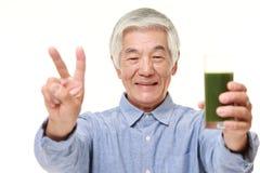 Homme japonais supérieur avec le jus de légumes vert Photos stock