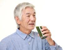 Homme japonais supérieur avec le jus de légumes vert Photos libres de droits