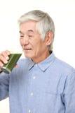Homme japonais supérieur avec le jus de légumes vert Photographie stock